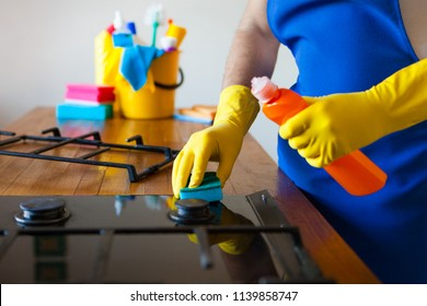 Young Men in rubber protective cleaning and polish cooker. Black shiny surface of kitchen top, hands, detergent. Set cleaning concept