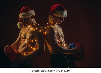 Young men in santa costume, present for girls. New year strip and gifts for adults. Call boys or sexy athlete men at xmas. Twins santa with muscular body in garland. Christmas party and sex games.
