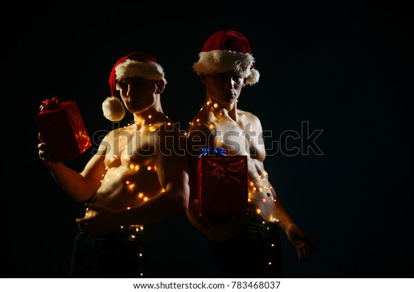 Young men in santa costume, present for girls. Christmas party and sex games. New year strip and gifts for adults. Call boys or sexy athlete men at xmas. Twins santa with muscular body in garland.
