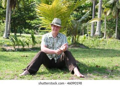 Young men sittin under palm