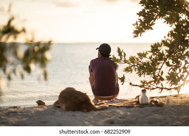 Young men sitting on the sand wearing a hat, looking at the sunset with his dog next to him.