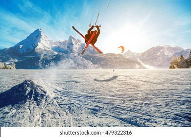 Young men, skiing on frozen lake in the mountains, in the rays of the rising sun, in winter, on vacation