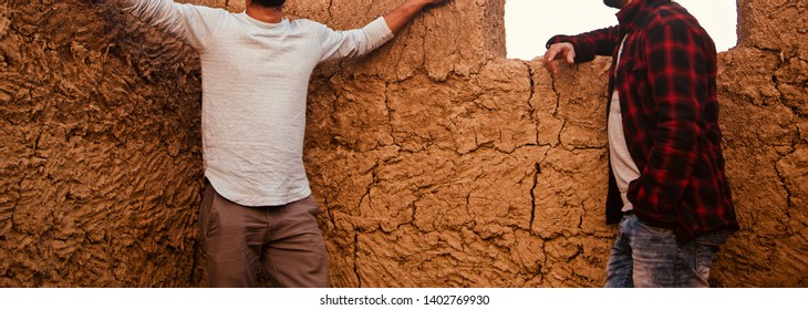 Young men standing around a clay made structure isolated unique photo