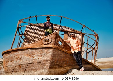 Young men standing in an old metallic boat around a coastal area
