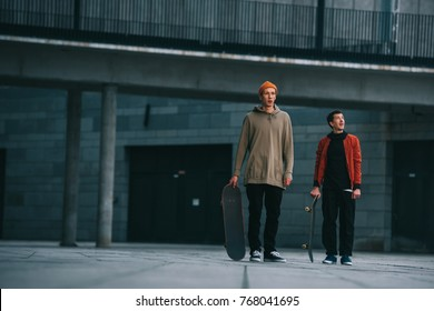 young men in streetwear outfit standing with skateboards