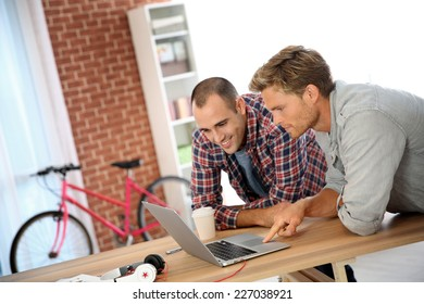 Young men studying in front of laptop