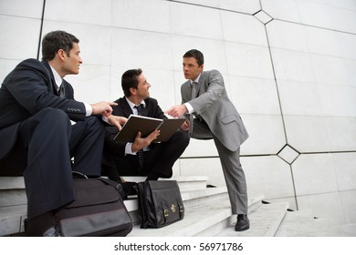 Young men in suit sitting on steps of stairs