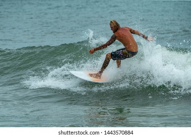 Young men surfers ride the ocean tropical wave in Vietnam