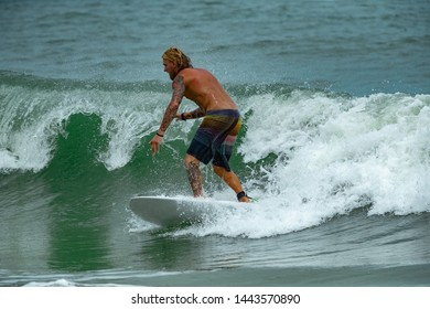 Young men surfers ride the ocean tropical wave in Bali