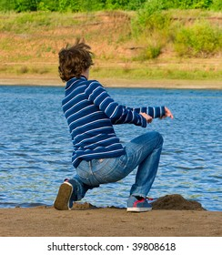 Young men throws stone into the river against summer landscape