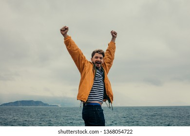 Young men traveler with raised arms on his road trip to the sea