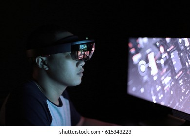 Young men trying Virtual Reality with Microsoft HoloLens in dark room