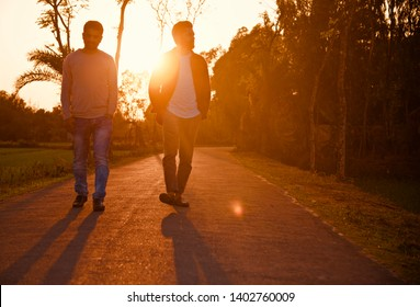 Young men walking around an empty road in the afternoon
