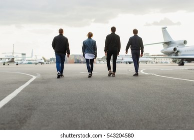 Young men walking on airfield