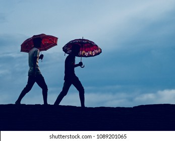 Young men walking on a high place together holding umbrellas in hand isolated unique photo