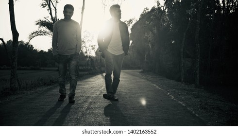Young men walking together on an empty street black and white photo