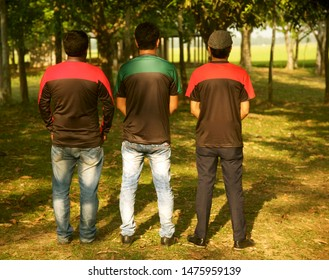 Young men wearing jeans standing together around a place