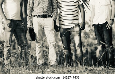 Young men wearing stylish dress standing together around a place