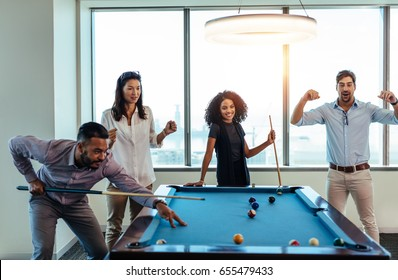 Young men and woman playing billiards at office after work. Business colleagues involving in recreational activity after work.