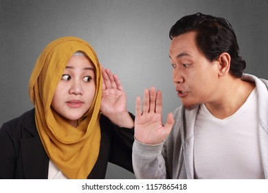 Young Men and women asian muslim wisper on each other