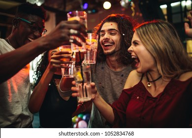 Young men and women celebrating a party, drinking and dancing. Group of friend toasting drinks and having fun at the nightclub.