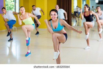 Young men and women are dancing aerobics in dance class.