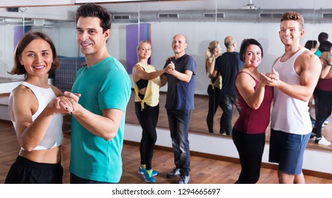 Young men and women dancing salsa o bachata in a dance hall