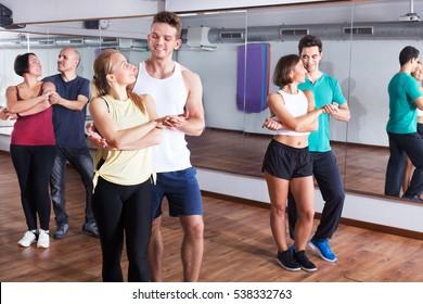 Young men and women dancing the salsa o bachata at the dance hall