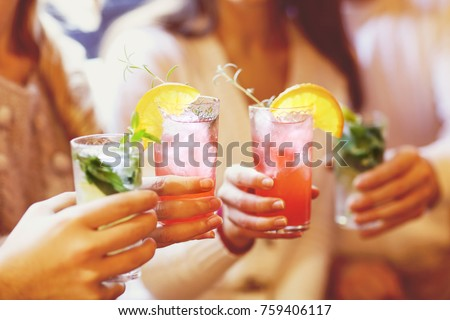 Young men and women drinking cocktail at party
