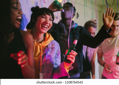 Young men and women enjoying at the house party. Friends laughing and dancing holding drinks at house party.