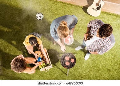Young men and women grilling meat and drinking beer on green grass at picnic