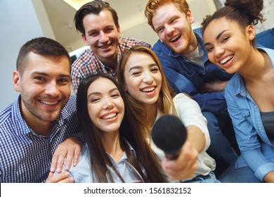 Young men and women having fun together indoors giving mike to photographer close-up smiling happy offer to sing