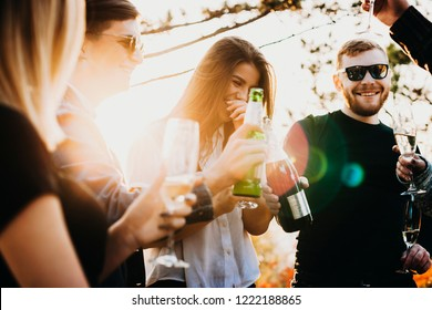 Young men and women laughing and drinking fine alcohol while spending time in nature on sunny day