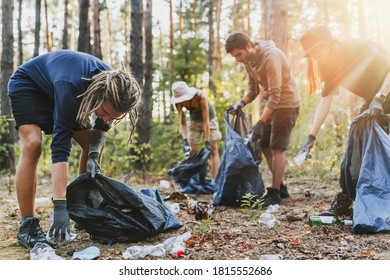 Young men and women picking up litter in forest - Shutterstock ID 1815552686
