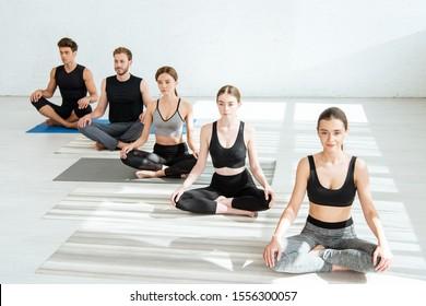 young men and women practicing yoga in half lotus pose