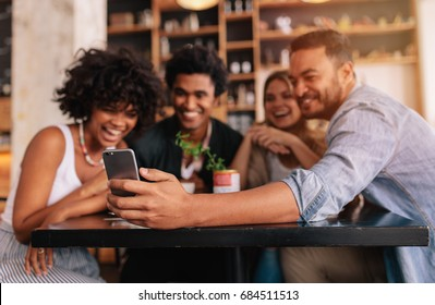 Young men and women sitting at cafe table and taking a self portrait with mobile phone. Multiracial group of friends taking selfie on smart phone at coffee shop.