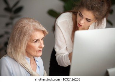 Young mentor teaching senior colleague explaining computer work, corporate teacher training helping focused aged woman with problem or online task, giving instructions to old employee at workplace