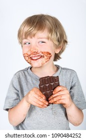 Young messy boy eating a chocolate bar with chocolate on his face