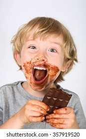 Young messy boy eating a chocolate bar with chocolate on his face and hands