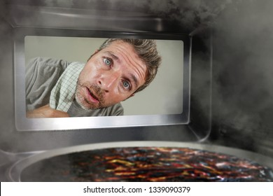 young messy and funny dummy man in the kitchen looking through microwave or oven pizza burning overcooked making a mess of home cook in domestic disaster and lifestyle concept