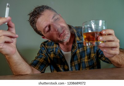 young messy and wasted addict man smoking cigarette having alcoholic drink looking at whiskey glass suffering alcoholism and tobacco addiction in unhealthy habit concept and alcohol abuse