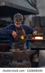 Young metalworker or blacksmith working with red hot metal in a workshop forming it into a coil with a mallet on an anvil