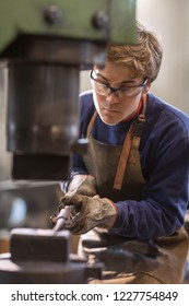 Young metalworker or blaksmith working with hot metal in a workshop holding it in a mold using specialist tongs leaning forward with concentration to watch his work