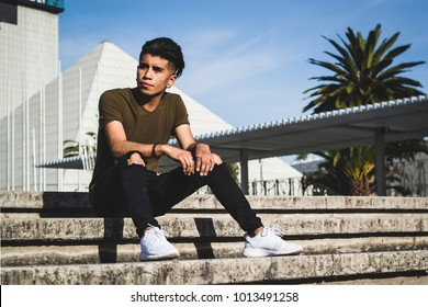 Young mexican hipster fashion with serious poses and black glasses in a minimalist environment