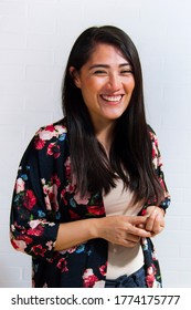 Young mexican latin woman laughing naturally in semi formal dress.