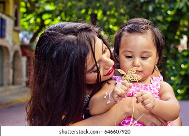 young mexican mother is holding her daughter an playing with a plastic flower on the street.