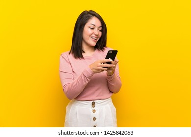 Young Mexican woman over isolated yellow background sending a message with the mobile