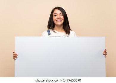 Young Mexican woman over isolated background holding an empty white placard for insert a concept