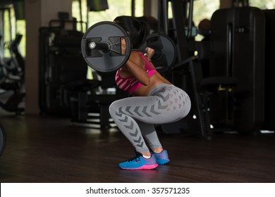 Young Mexican Woman Working Out Legs With Barbell In Fitness Center - Squat