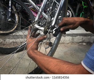 young mexican worker, latino, fixing bicycle puncture